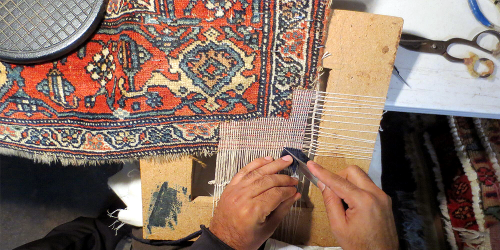 One of our rug reweavers working on a Persian rug repair.